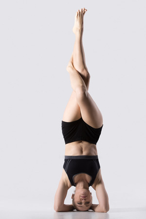 headstand: Sporty beautiful young woman practicing yoga, doing variation of supported headstand, garuda salamba sirsasana with crossed legs, working out wearing black sportswear, studio, full length