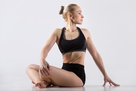 sukhasana: Sporty beautiful happy young woman practicing yoga, sitting in cross legged position, Revolved Easy Pose, Spinal Twist, Parivrtta Sukhasana, working out wearing black sportswear, studio