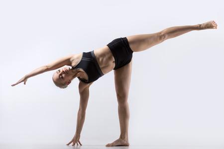 chandrasana: Sporty beautiful young woman practicing yoga, standing in Ardha Chandrasana posture, Half Moon Pose, working out wearing black sportswear, studio full length, grey background
