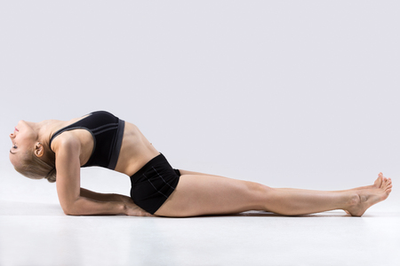 poses de modelos: Sporty beautiful young woman practicing yoga, doing easy variation of Matsyasana, Fish pose with straight legs, yoga for relieving stress, working out wearing black sportswear, studio
