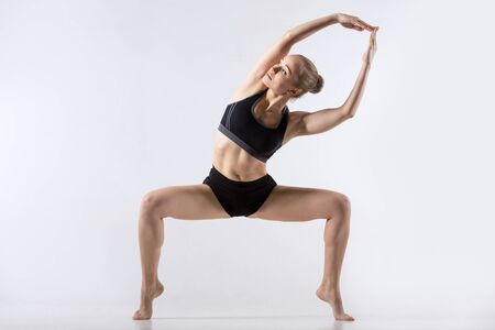 tiptoes: Sporty beautiful young woman practicing yoga, doing side bend variation of Goddess, Temple or Sumo Squat Pose, working out wearing black sportswear, studio full length, grey background