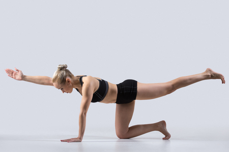 aerobic training: Sporty beautiful young woman practicing yoga, doing balance exercise bird dog, kneeling opposite arm and leg extension, asana sunbird (chakravakasana), working out wearing black sportswear, studio Stock Photo