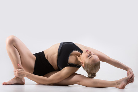 revolved: Sporty beautiful young woman practicing yoga, doing variation of Parivrtta Janu Sirsasana, Revolved Head-to-Knee Forward Bend Pose, working out wearing black sportswear, studio