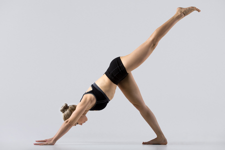 pada: Sporty beautiful young woman practicing yoga, doing one-legged downward facing dog pose, eka pada adho mukha svanasana, working out wearing black sportswear, studio, full length, side view Stock Photo