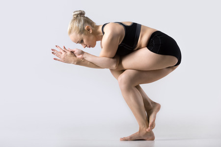 beautiful ankles: Sporty beautiful young woman practicing yoga, doing Eagle Fold Pose, variation of Garudasana, exercise for ankles, calves, thighs, hips and shoulders, working out wearing black sportswear, studio