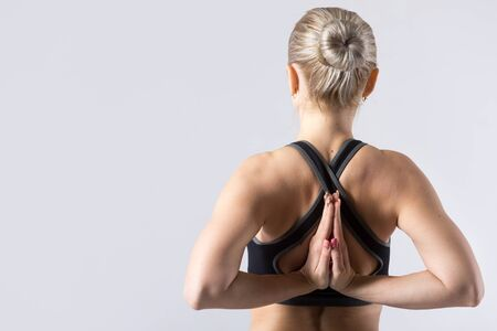 anjali: Sporty beautiful young woman practicing yoga, holding Anjali Mudra behind the back, exercise for flexibility in the hands, wrists, arms, shoulders, studio, back view, copy space, close-up