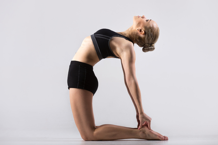 ushtrasana: Sporty beautiful young woman practicing yoga, doing Ushtrasana, Camel Pose, working out wearing black sportswear, studio, full length