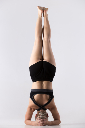 shirshasana: Sporty beautiful young woman practicing yoga, doing supported headstand, salamba sirsasana, working out wearing black sportswear, studio, full length, back view Stock Photo