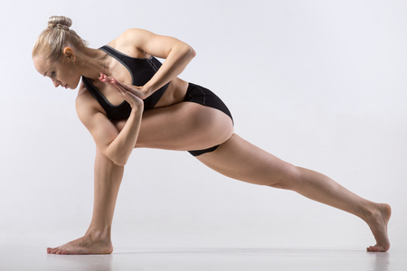 side angle pose: Sporty beautiful young woman practicing yoga, doing lunge exercise, Revolved Side Angle Pose, Parivrtta Parsvakonasana, working out wearing black sportswear, studio full length, grey background