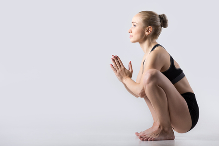 yogi: Sporty beautiful young woman practicing yoga, sitting in squat, Garland Pose, Malasana, stretching back muscles, hips, ankles, working out wearing black sportswear, studio