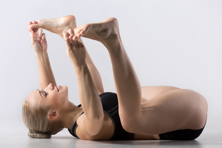 relieving pain: Sporty beautiful young woman practicing yoga, working out, doing Happy Baby (Dead Bug) Pose, Ananda Balasana, relaxing, stretching spine, legs, relieving back pain, stress and fatigue, studio