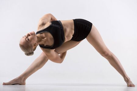 trikonasana: Sporty beautiful young woman practicing yoga, standing in Bound Triangle posture, Baddha Trikonasana, working out wearing black sportswear, studio full length, grey background