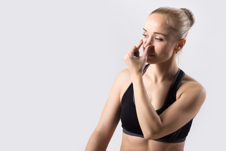 nostril: Portrait of sporty beautiful young woman practicing yoga, nadi shodhana pranayama (Alternate Nostril Breathing), copy space, studio Stock Photo