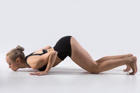 ashtanga: Sporty beautiful young woman practicing yoga, working out, doing easy alternative to Chaturanga Dandasana, half push-up, Eight-Limbed or Caterpillar pose, Ashtanga Namaskara, studio