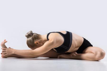 Sportieve mooie jonge vrouw het beoefenen van yoga, doen Janu Sirsasana, Head-to-Knee Forward Bend Pose, uit te werken, gekleed in zwarte sportkleding, studio, volledige lengte