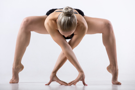 namaste: Sporty beautiful young woman practicing yoga, bending in variation of Goddess, Temple or Sumo Squat Pose, working out wearing black sportswear, studio full length, grey background Stock Photo