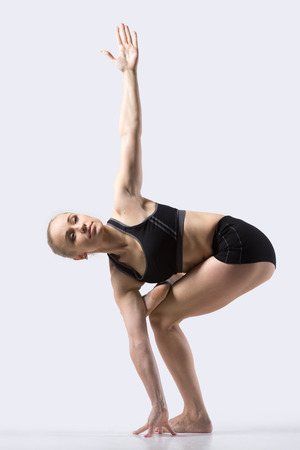 revolved: Sporty beautiful young woman practicing yoga, doing Variation of Revolved Chair Pose, Eka Pada Padma Parivritta Utkatasana, working out wearing black sportswear, studio full length, side view Stock Photo