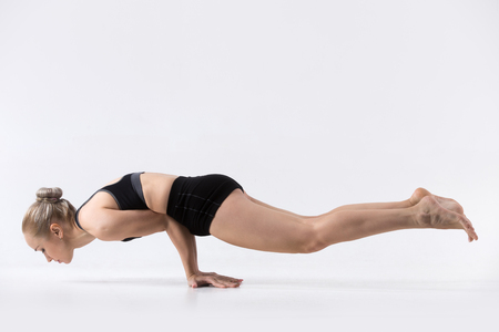 poses: Sporty beautiful young woman practicing yoga, doing handstand Peacock pose, Mayurasana, toning up abdominal muscles, forearms, wrists and elbows, working out wearing black sportswear, studio