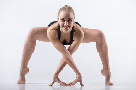 tiptoes: Portrait of sporty beautiful young cheerful woman practicing yoga, bending in variation of Goddess, Temple or Sumo Squat Pose, working out wearing black sportswear, studio full length, grey background