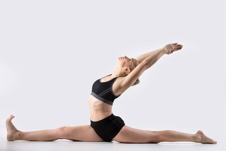 Sporty beautiful young woman practicing yoga, doing Splits Exercise, Hanumanasana, Monkey God Pose, stretching the thighs, hamstrings, groins, working out wearing black sportswear, studio, full length Stock Photo