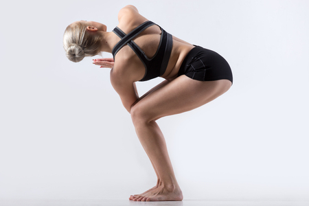 parivrtta: Sporty beautiful young woman practicing yoga, doing Revolved Chair Pose, Parivrtta Utkatasana, working out wearing black sportswear, studio full length, grey background, back view