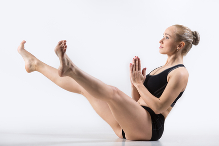 straddle: Sporty beautiful young woman practicing yoga, doing Wide-Legged Boat Pose, Prasarita Navasana, for abdomen, hamstrings, inner thighs and groin, working out wearing black sportswear, studio