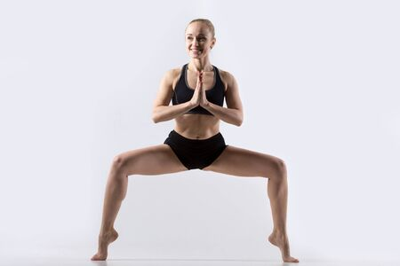 tiptoes: Sporty beautiful young cheerful woman practicing yoga, standing in Goddess, Temple or Sumo Squat Pose, working out wearing black sportswear, studio full length, grey background