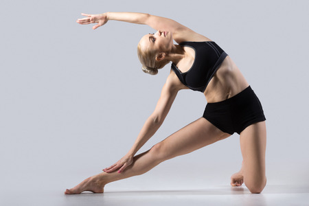 to bend: Sporty beautiful young woman practicing yoga, doing side bend Parighasana, Gate Pose, working out wearing black sportswear, studio, full length