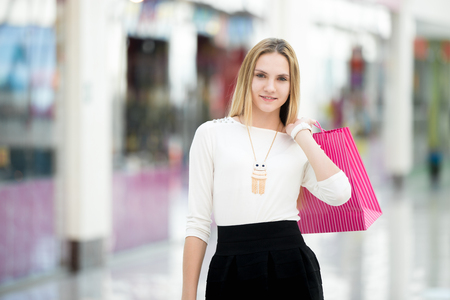 errands: Cheerful beautiful young woman shopping, holding paper bags, walking beside shopwindows in mall, copyspace