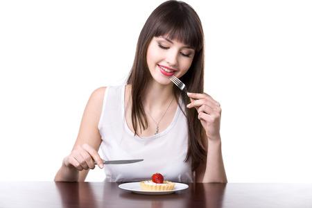 dudando: La mujer sonriente linda joven que se sienta delante de la placa con la torta deliciosa tarta de la fresa en la cesta de la masa, la celebración de cuchillo y tenedor, la decisión de probar el postre dulce, estudio, fondo blanco, aislado Foto de archivo