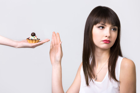 willpower: Young resolute dieting beautiful woman refusing tart cake with cream and chocolate, studio, healthy lifestyle concept, gray background, isolated Stock Photo