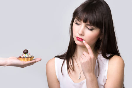 dudando: Young dieting beautiful woman sitting in front of delicious cream and chocolate tart cake, looking at it appraisingly, healthy lifestyle concept, studio, gray background, isolated, copy space