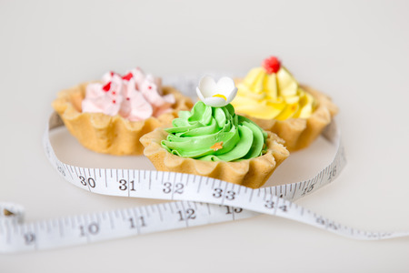 unhealthy lifestyle: Three colorful green, pink and yellow tart cakes wrapped in measuring tape on white background, unhealthy lifestyle concept, studio