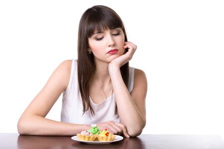 dudando: Mujer de dieta joven sentado delante de la placa con las tortas tarta deliciosa crema en cestas de masa, mirando a la postre dulce con infeliz expresión y hambriento, estudio, fondo blanco, aislado