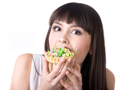 smudgy: Young beautiful hungry woman eating very delicious tart cake with covered in cream face. Diet failure concept. Studio, white background, isolated Stock Photo