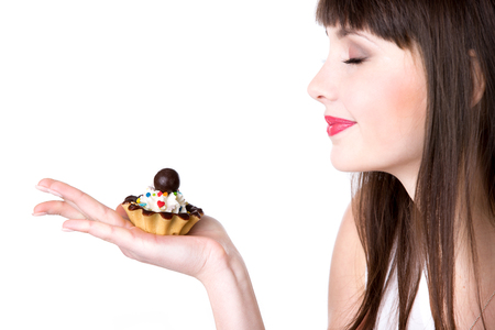 Young smiling woman holding in her palm delicious tart cake with cream and chocolate, beautiful cheerful female teen model enjoying smell of the food, studio, white background, copyspace Stock Photo