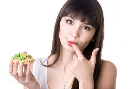 Young attractive playful hungry woman licking her covered in cream fingers while eating very tasty tart cake. Studio, white background, isolated Stock Photo