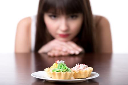 Young dieting woman sitting in front of plate with delicious cream tart cakes, looking at forbidden food with unhappy and hungry expression, studio, white background, isolated, close-up Stockfoto