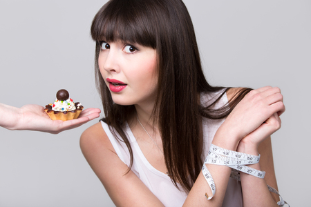 Young dieting woman with hands tied with measurement tape sitting in front of tart cake, got caught while trying to reach it and take a bite, studio, gray background, isolated Stock Photo