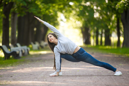 utthita: Smiling beautiful sporty young woman working out in park alley, doing warming up lunge exercise, Utthita Parsvakonasana, Extended Side Angle Pose, full length Stock Photo