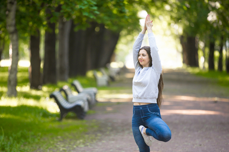 vriksasana: Portrait of smiling beautiful sporty young woman working out in park alley, doing stretching exercise, standing in asana Vrikshasana (Vriksasana, Tree Posture), hands above head
