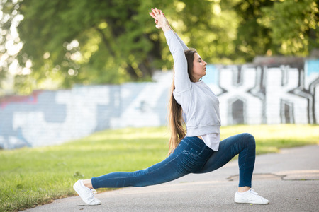 Beautiful sporty young woman working out on city street, doing warming up lunge exercise, High Crescent Pose, warrior 1, sun salutation complex, full length