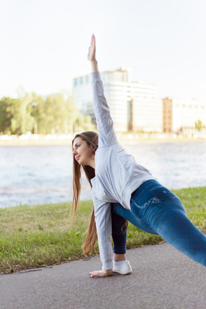 utthita: Beautiful sporty young woman working out on city street on riverbank, doing warming up lunge exercise, Utthita Parsvakonasana, Extended Side Angle Pose, full length