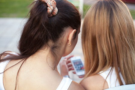 Two cute beautiful young women friends sitting on park bench on summer day, browsing social media pictures on smartphone, back view, focus on girls