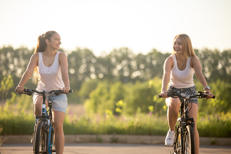 Two beautiful young women riding bikes wearing casual white tank tops and jeans shorts in park on bright sunny summer day, laughing together, having good time Stock Photo