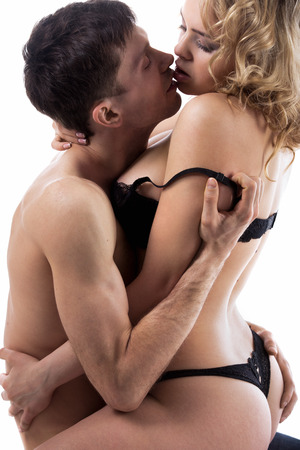naked young people: Young half naked couple kissing before making love, guy embracing, undressing girl in black lingerie, studio low key shot, white background