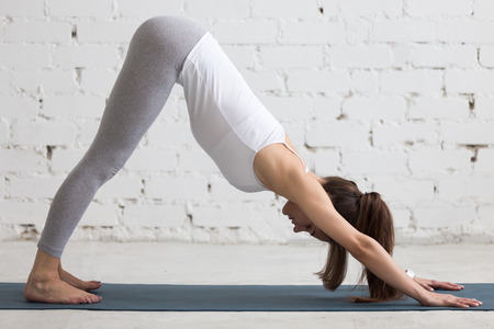 Beautiful young woman working out indoors, doing yoga exercise in the room with white walls, downward facing dog pose, adho mukha svanasana (sun salutation pose), full length, side view