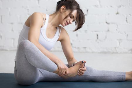 lesionado: La mujer joven hermosa sensación de dolor en el pie durante el entrenamiento deportivo en el interior, primer plano Foto de archivo