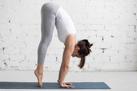 Beautiful young woman working out in loft interior, doing yoga exercise on blue mat, preparation for handstand, side view, full length