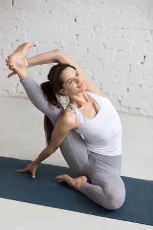 parivrtta: Beautiful smiling young woman working out indoors, doing yoga exercise on blue mat, sitting in Parivrtta Surya Yantrasana, Compass or Sundial Posture, full length